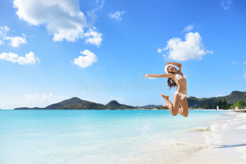 Happy Christmas hat girl jumping of joy on beach stock photos