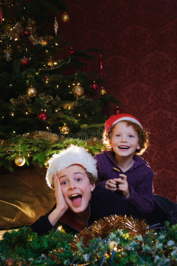 Happy Christmas kids. Two boys with christmas hats in front of a decorated christmas tree, surprised and laughing with joy stock image