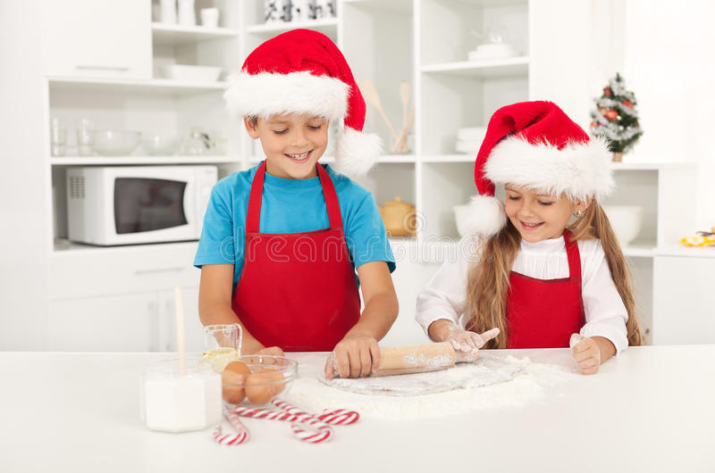Happy christmas kids stretching the cookie dough royalty free stock images