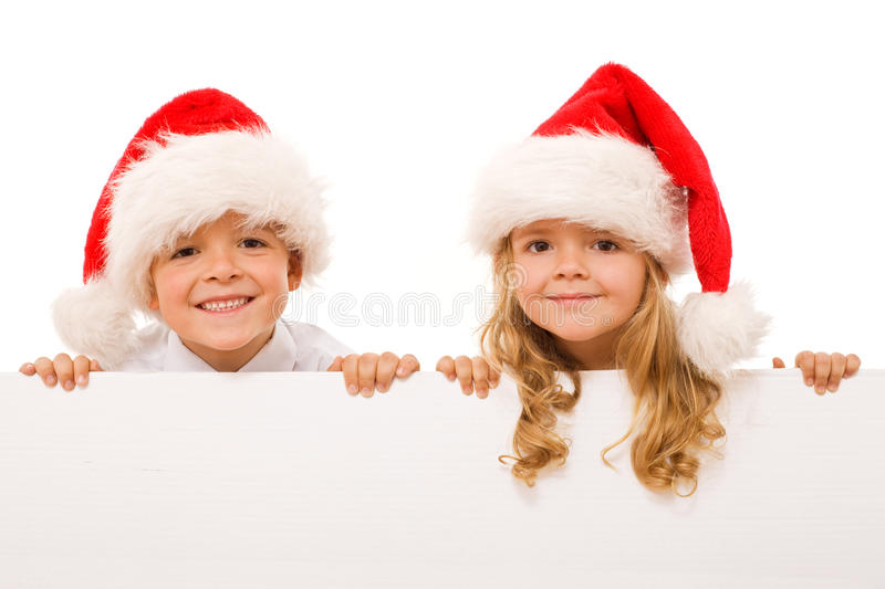 Happy christmas kids with white sign - isolated. Happy kids with santa hats and white cardboard - isolated christmas message, closeup stock image