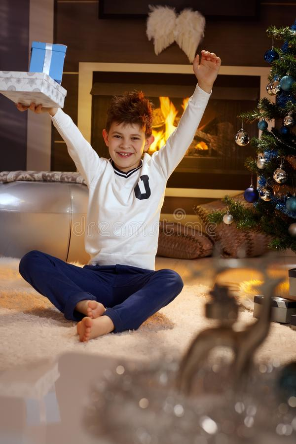 Happy christmas. Happy little boy lifting up high christmas present, smiling royalty free stock photos