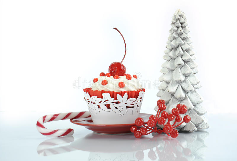 Happy Christmas red velvet cupcake. With cherry and tree on reflective white background stock photo