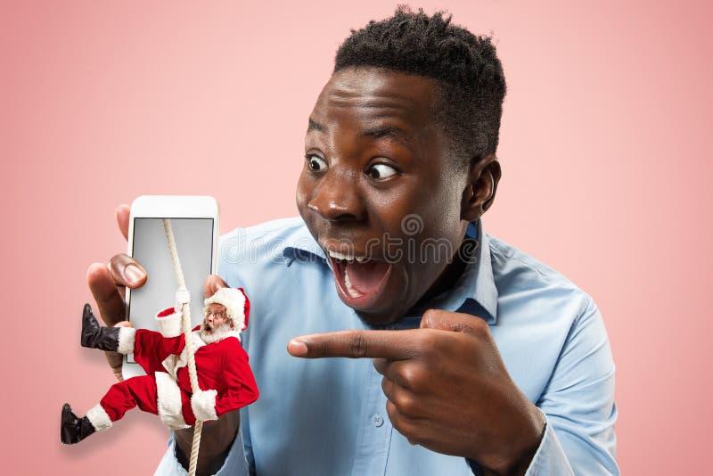 Happy Christmas Santa Claus on studio background. Happy Christmas Santa Claus in screen of phone on coral studio background. Caucasian male model pointing on men stock photo
