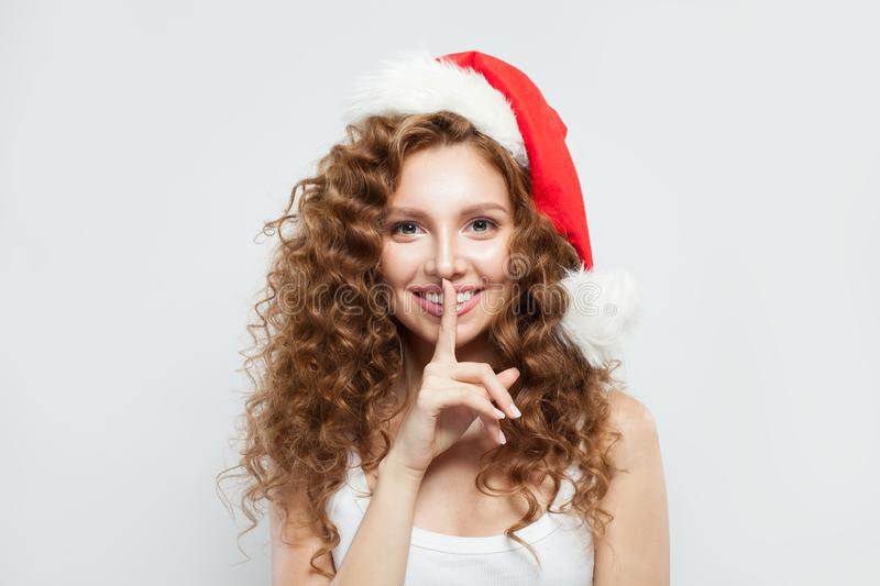 Happy Christmas woman in Santa hat asks to be quiet on white background. Shhh! Gifts here royalty free stock photos