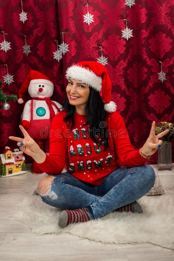 Happy woman showing victory sign. Happy Christmas woman sitting down with legs crossed and showing victory sign stock photos