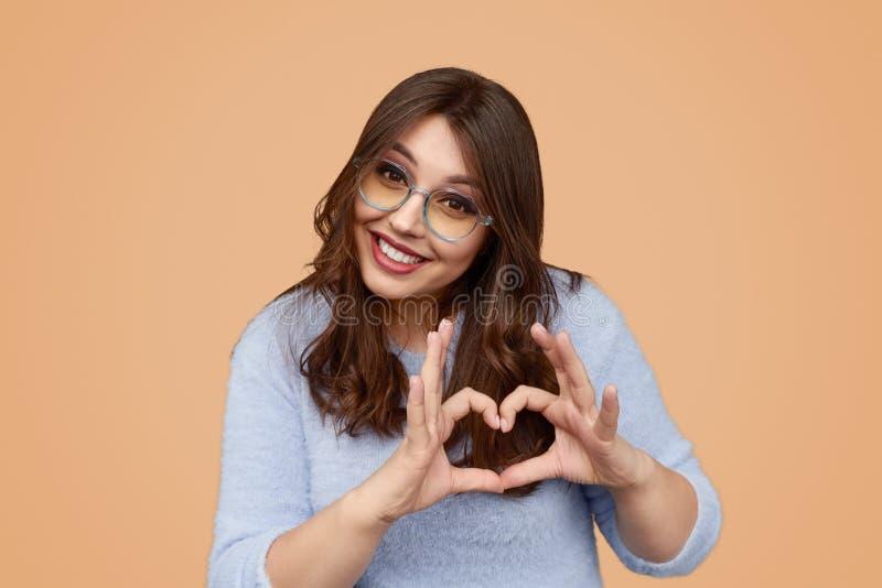 Happy chunky female gesturing heart stock photo