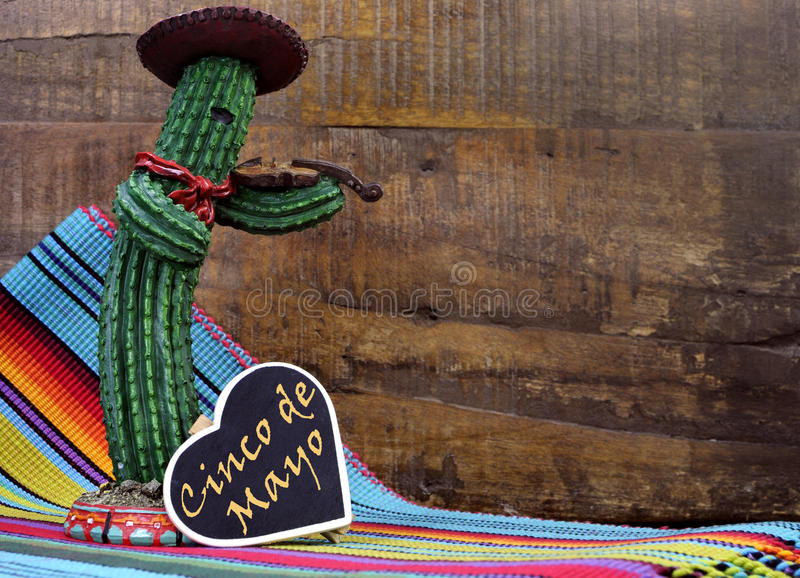 Happy Cinco de Mayo, 5th May, party celebration with with fun Mexican cactus and blackboard sign. With text against a dark retro wood background royalty free stock image