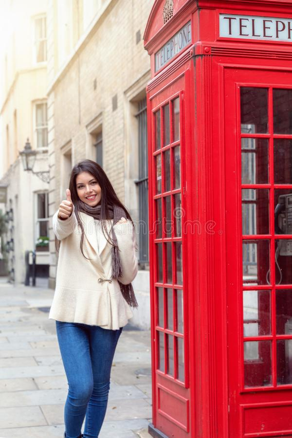 Happy city traveler woman stands next to a red telephone booth n London. And shows the thumbs up sign royalty free stock photography