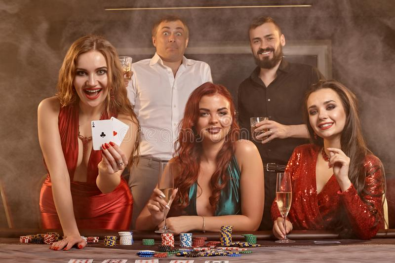 Group of a young wealthy friends are playing poker at a casino. stock photo