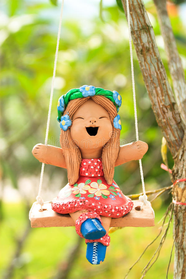 Happy Clay doll playing swing