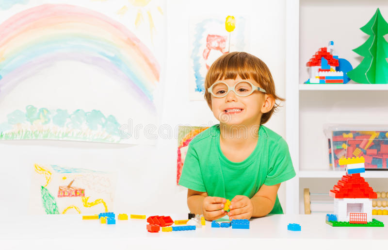 Happy clever little boy play with blocks. Portrait of clever looking little preschool boy in glasses playing with plastic blocks constructing simple house in the stock photography