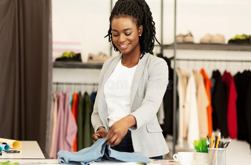 Smiling Black Woman Buying Designer Clothes In Fashionable Showroom. Happy Client. Cheerful Black Woman Buying Designer Clothes In Fashionable Store. Copy Space royalty free stock image