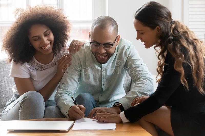 Happy clients signing agreement with or real estate agent. Smiling female mixed race lawyer or financial advisor showing satisfied african american family stock photography