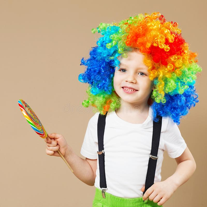 Happy clown boy in large colorful wig. Let`s party! Funny kid cl stock photos