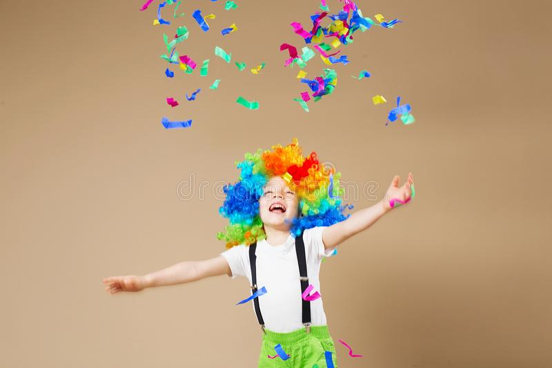 Happy clown boy with large colorful wig. Let`s party! Funny kid. Clown. 1 April Fool`s day concept. Portrait of a child throws up a multi-colored tinsel and stock photography