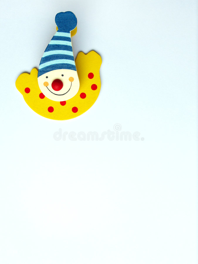 Happy clown paper clip. A cute design paper clip in the shape of a bright happy clown. Placed on a piece of white paper. Clean composition and background royalty free stock image