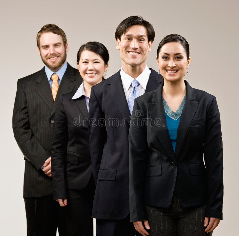 Happy co-workers wearing suits and posing royalty free stock photography