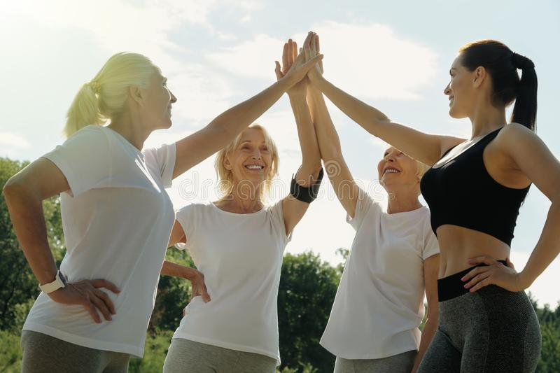 Happy coach and retired people high fiving after training stock photo