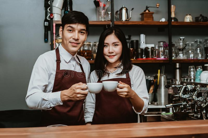 Happy coffee shop small business owner Asian couple wearing in apron holding coffee cups looking at camera while standing at bar royalty free stock images
