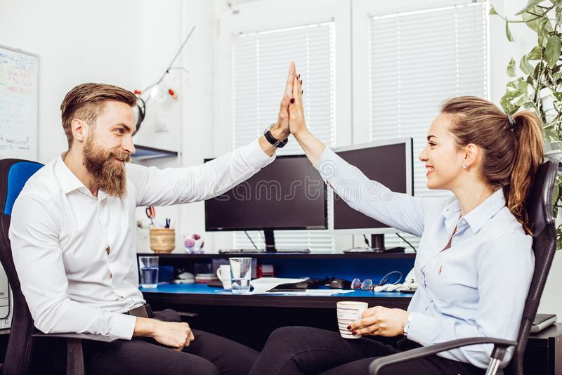Happy colleagues giving high five stock photography