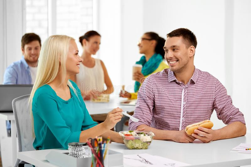 Happy colleagues having lunch and eating at office royalty free stock photography