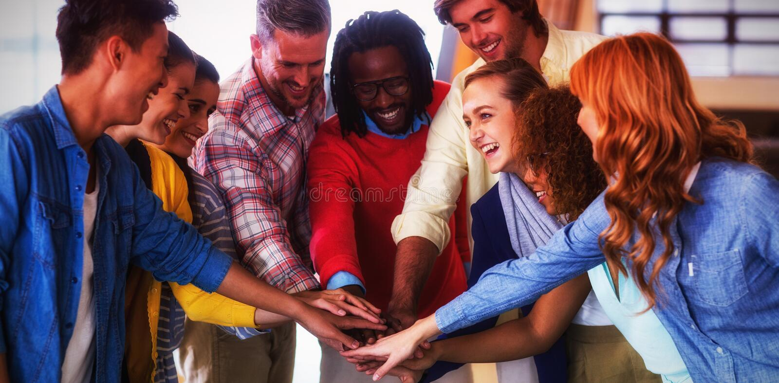 Happy colleagues piling up hands stock photography