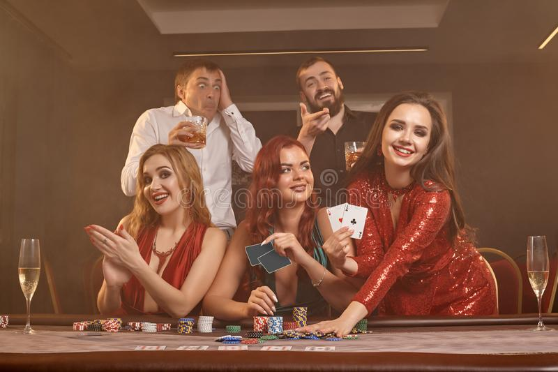 Group of a young wealthy friends are playing poker at a casino. stock photos