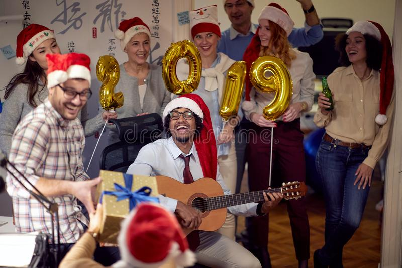 Happy colleagues in Santa caps having Christmas fun and play guitar stock images