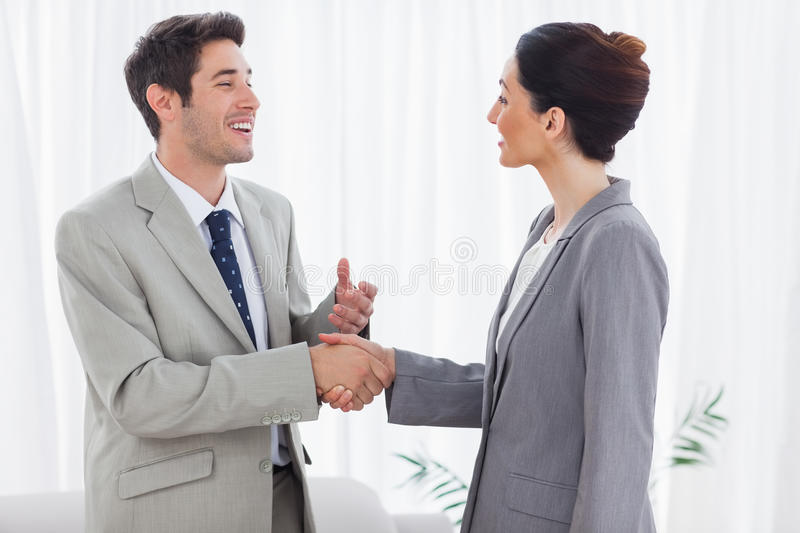 Happy colleagues shaking hands during meeting. At office royalty free stock images