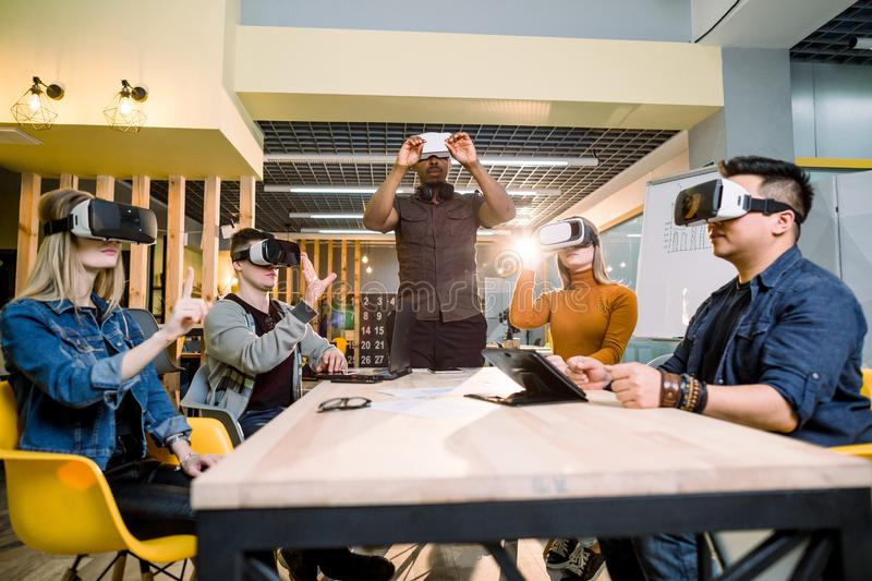 Happy colleagues testing vr glasses indoor. Virtual reality and wearable tech concept with young people having fun stock photo