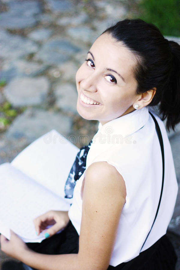 Happy college girl studying outdoors stock image