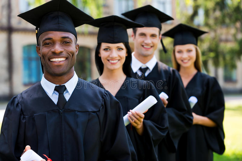 Happy college graduates. Four college graduates standing in a row and smiling royalty free stock photography