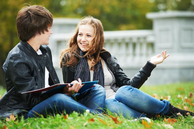 Happy college students on campus lawn outdoors. Happy college students on campus lawn, discussing. Caucasian royalty free stock image