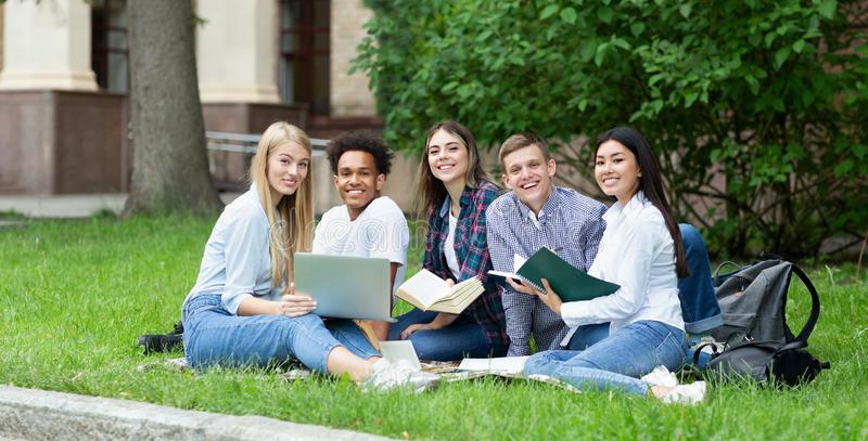 Happy college students resting in campus, smiling to camera royalty free stock images