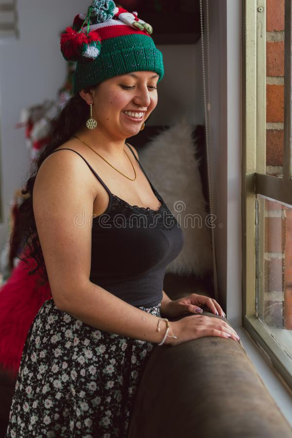 Happy Colombian woman at Christmas with Christmas hat looking out the window stock photography