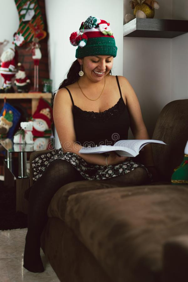 Colombian woman at Christmas sitting on the sofa reading a book royalty free stock photo