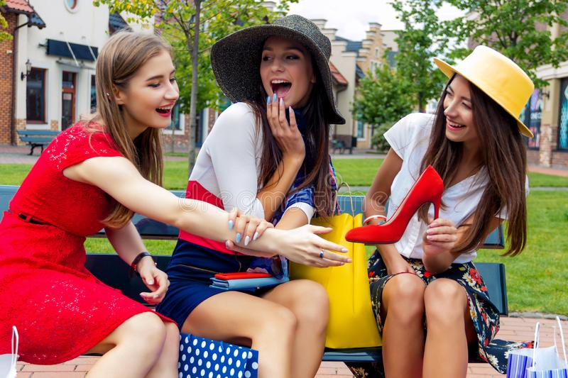 Fashion female women friends in shopping mall. Happy colorful women females adults girls friends in hats and colorful dresses sitting outdoor after shopping in royalty free stock photography