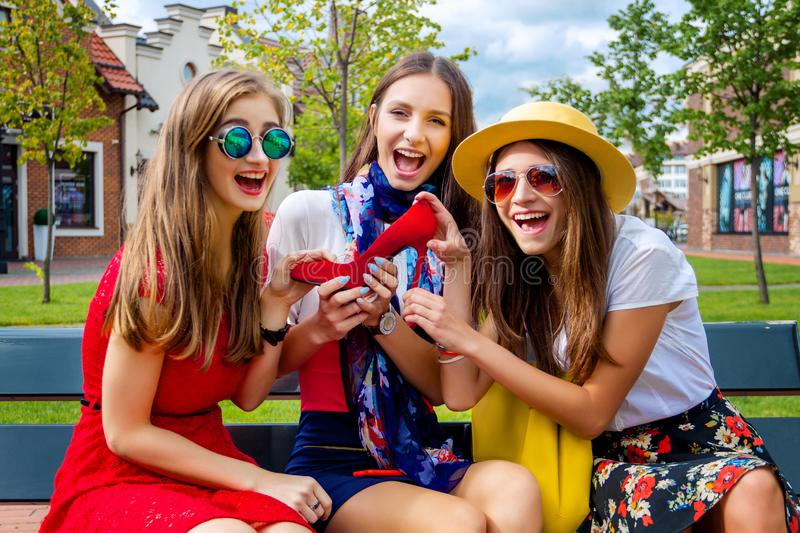 Fashion female women friends in shopping mall. Happy colorful women females adults girls friends in hats and colorful dresses sitting outdoor after shopping in royalty free stock image