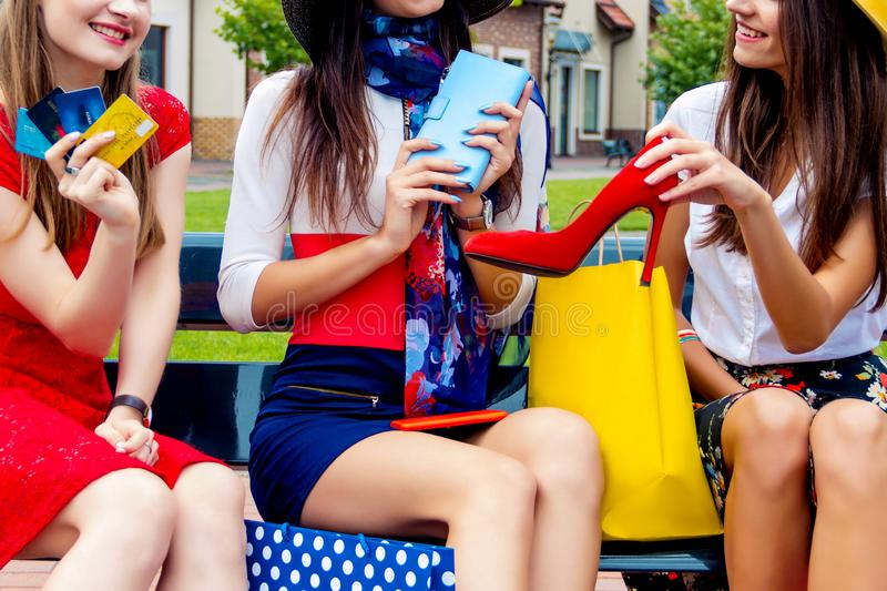 Fashion female women friends in shopping mall. Happy colorful women females adults girls friends in hats and colorful dresses sitting outdoor after shopping in stock images