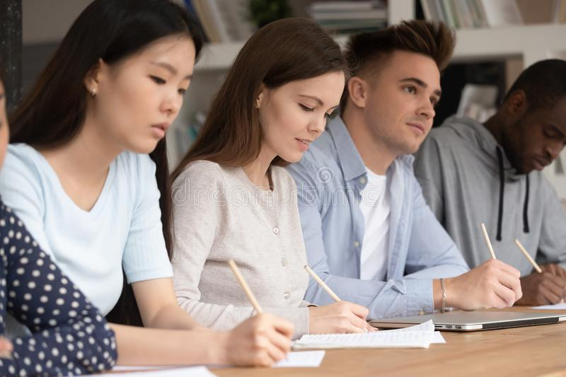 Happy concentrated mixed race students attending interesting lecture. royalty free stock photos
