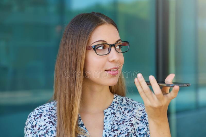 Happy confident business woman talking with mobile phone on speakerphone in the street stock photography