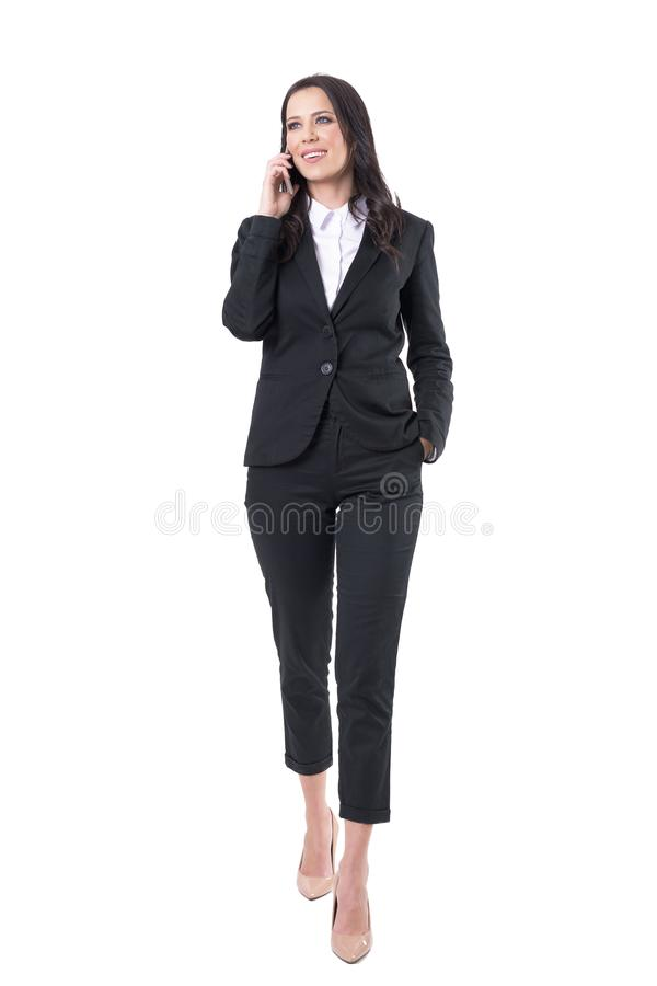 Happy confident business woman walking and talking on the cellphone looking away royalty free stock images