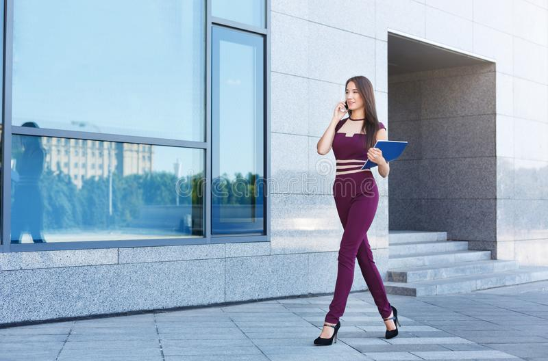 Confident young businesswoman talking on cell. Happy confident businesswoman walking near modern office center. Successful entrepreneur talking on smartphone and stock images