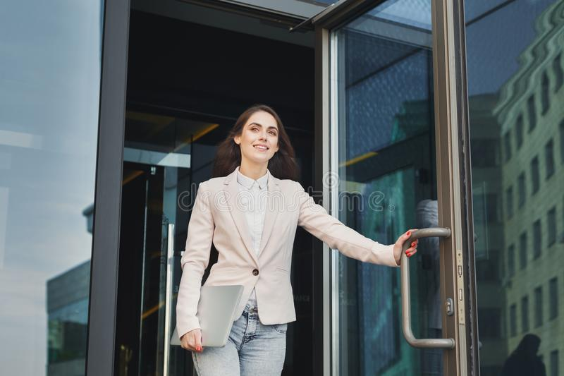 Confident young businesswoman talking on mobile. Happy confident businesswoman walking out of modern office center, holding laptop outdoors, copy space stock photography