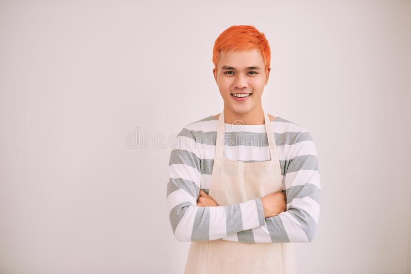 Happy and confident male cafe worker in apron smiling at a camera, standing. royalty free stock photography