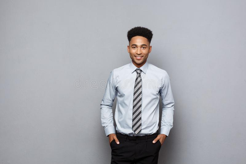 Business Concept - Happy confident professional african american businessman posing over grey background. stock image