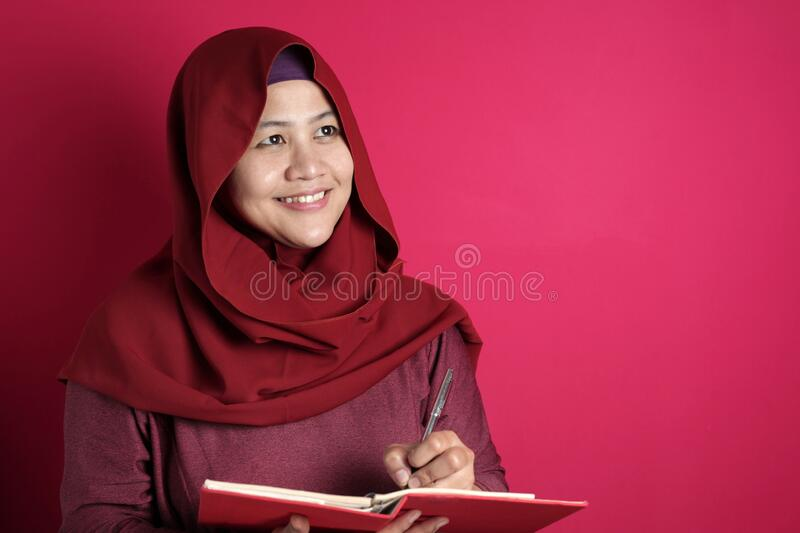Happy confident successful Asian muslim woman wearing hijab  writing on book, smiling and thinking. Educational literacy or jurnalism concept stock photos