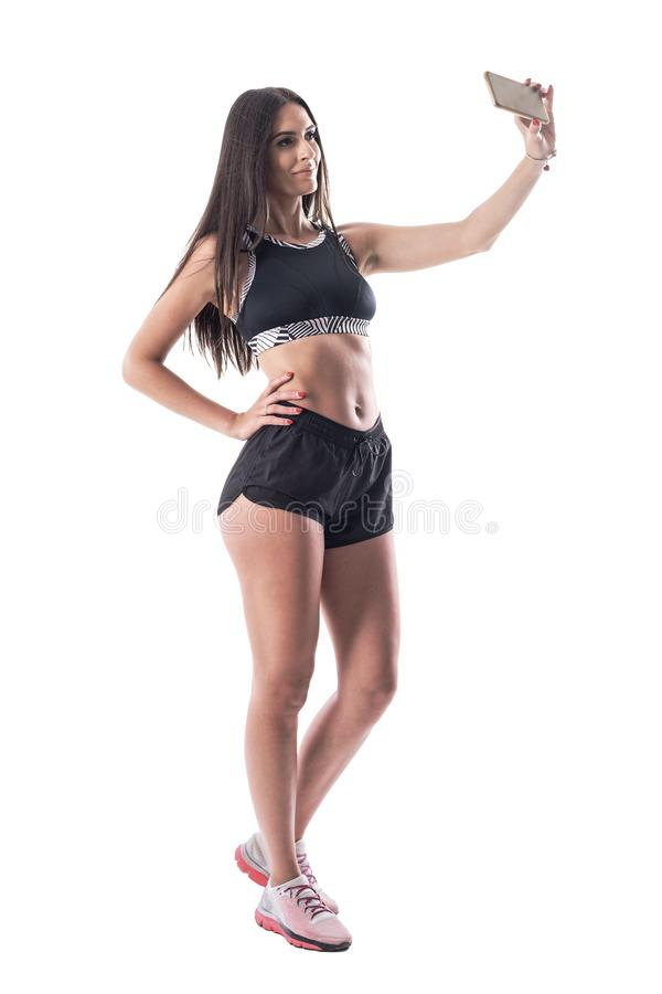 Happy confident young athletic gym woman taking selfie for social media with smartphone. stock image
