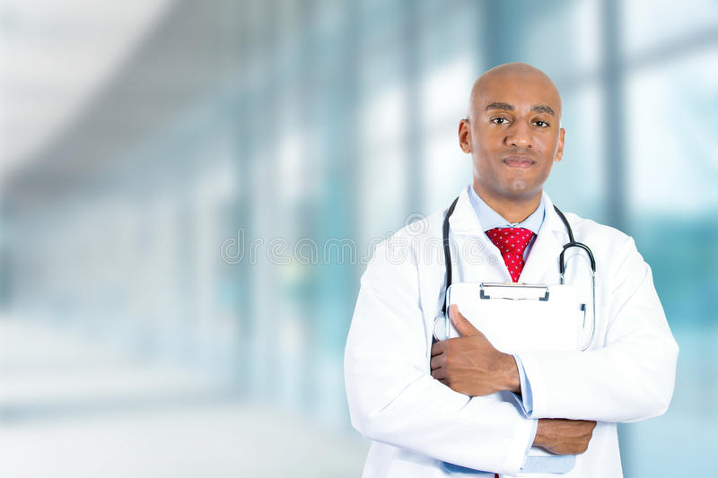 Happy confident young doctor standing in hospital hallway royalty free stock photo