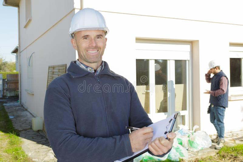 Happy construction inspector on building site writing on clipboard stock photography